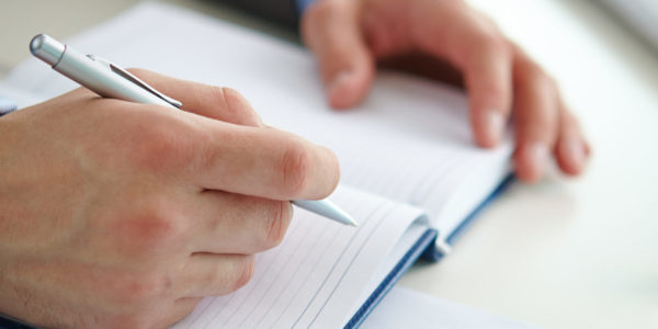 Businessman hand with pen over open notebook making report